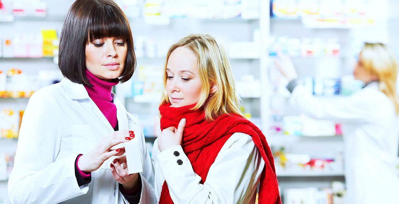 a pharmacist and a customer looking at a medicine