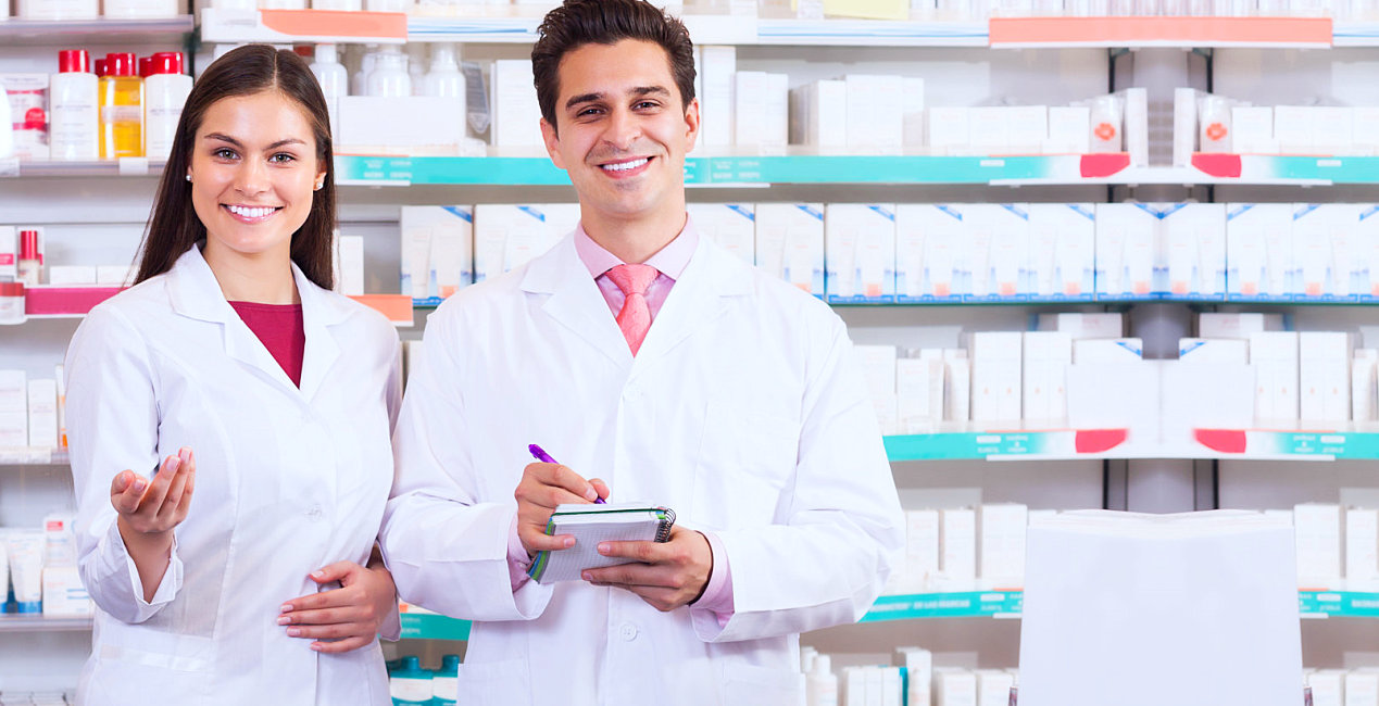 a male and a female pharmacist smiling, a room full of medicine in the background