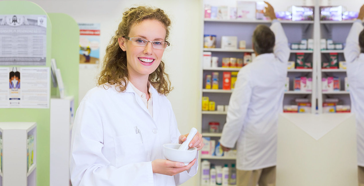 a pharmacist smiling while another pharmacist is reaching for a medicine on top of a shelf